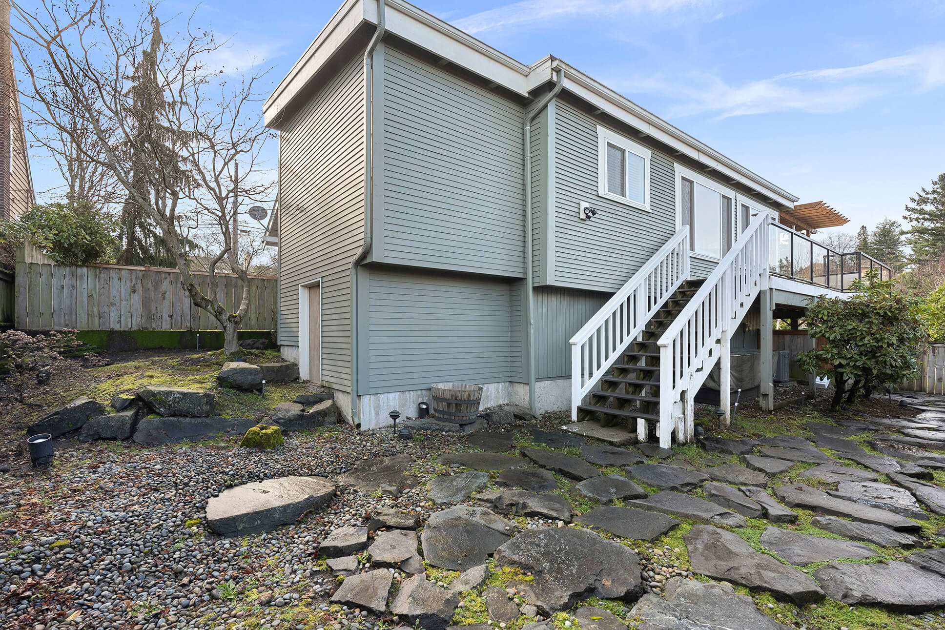 Stairs lead from view deck to fully fenced back yard