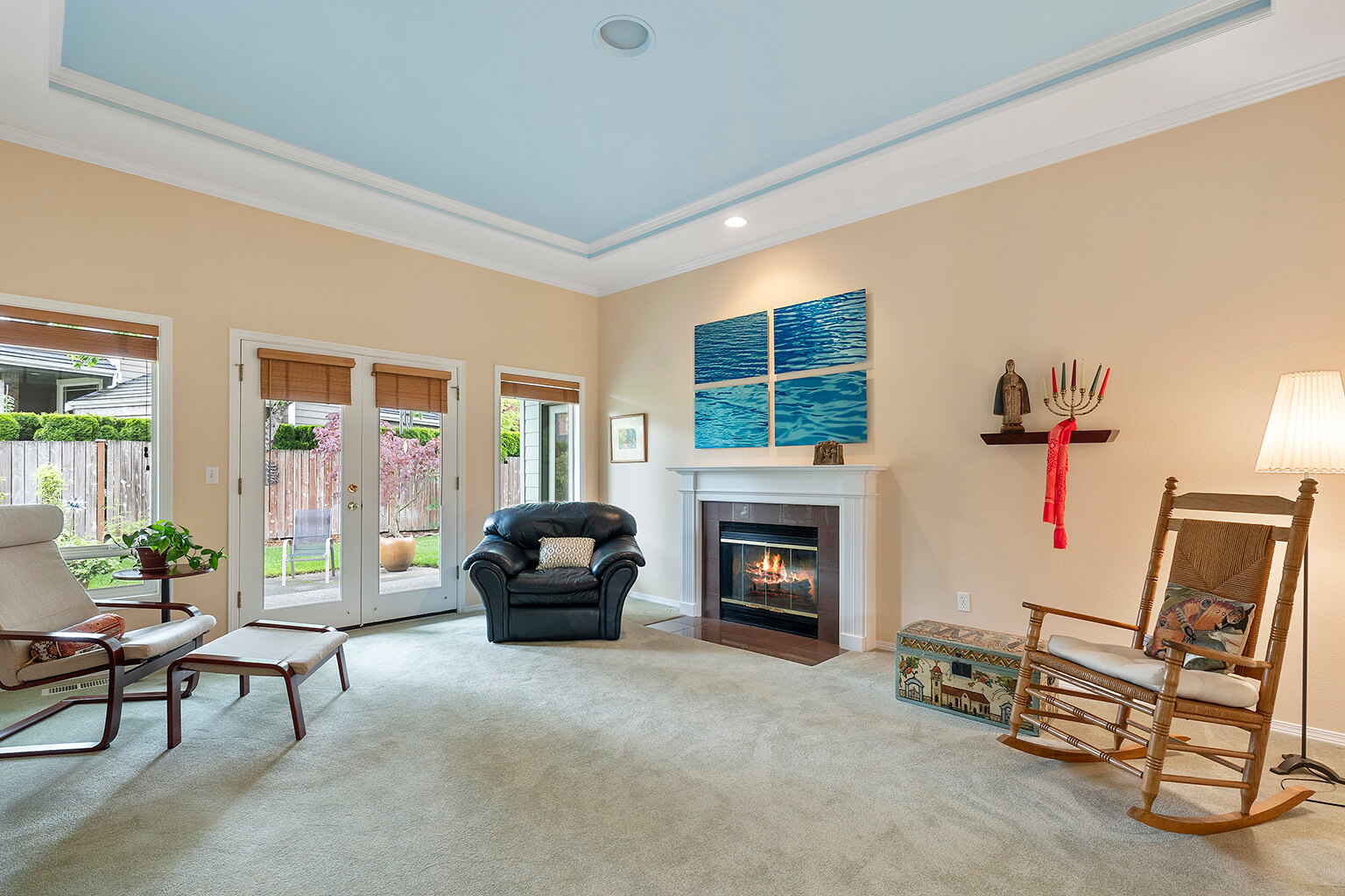 Living room features a wood burning fireplace with gas starter and French doors to a covered patio