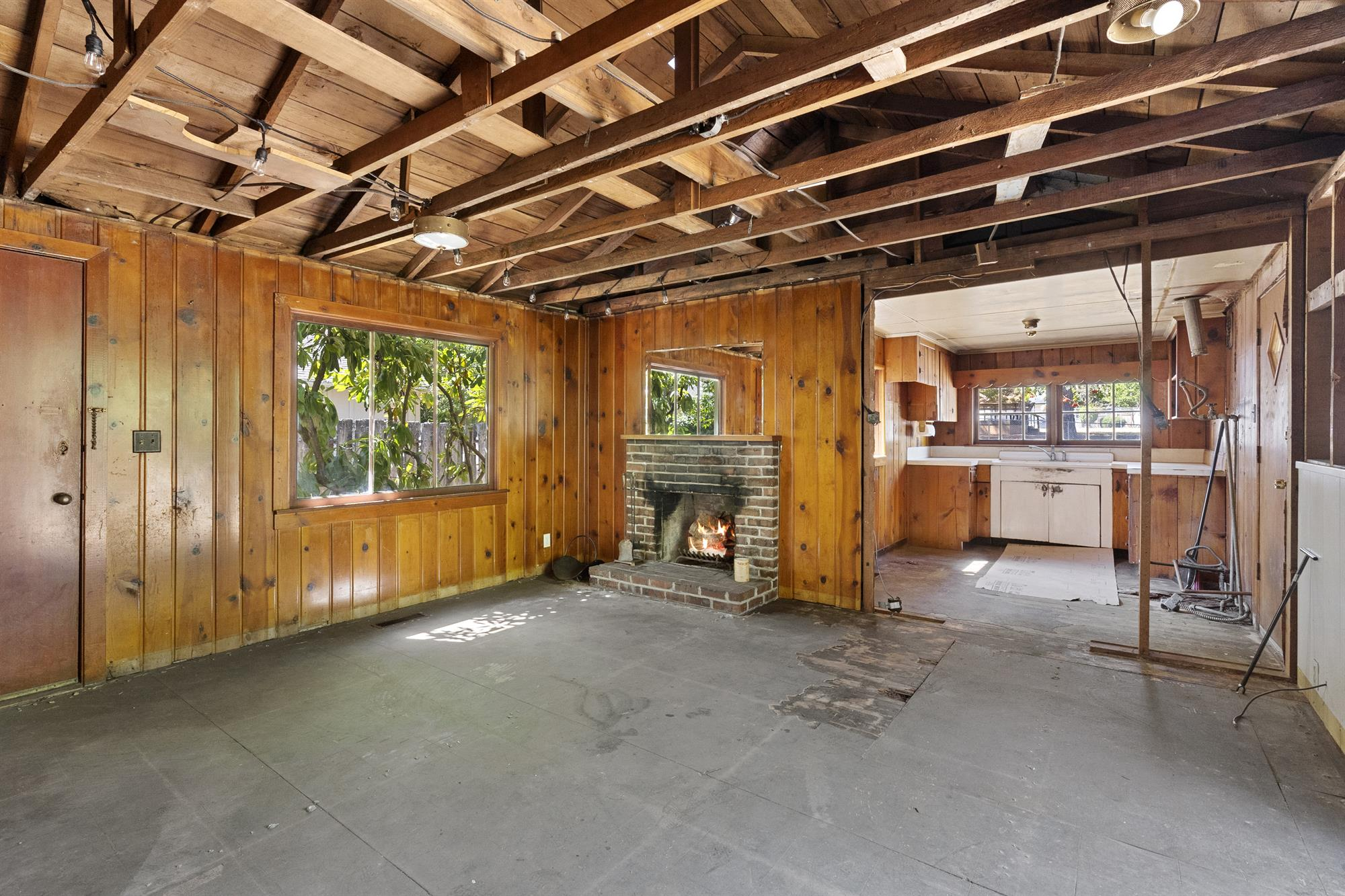 Living room with knotty pine paneling and wood burning fireplace