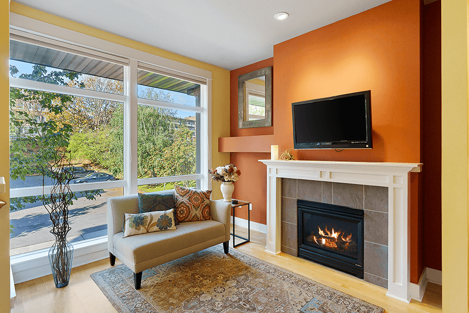 Floor to ceiling windows and a gas fireplace in the living area