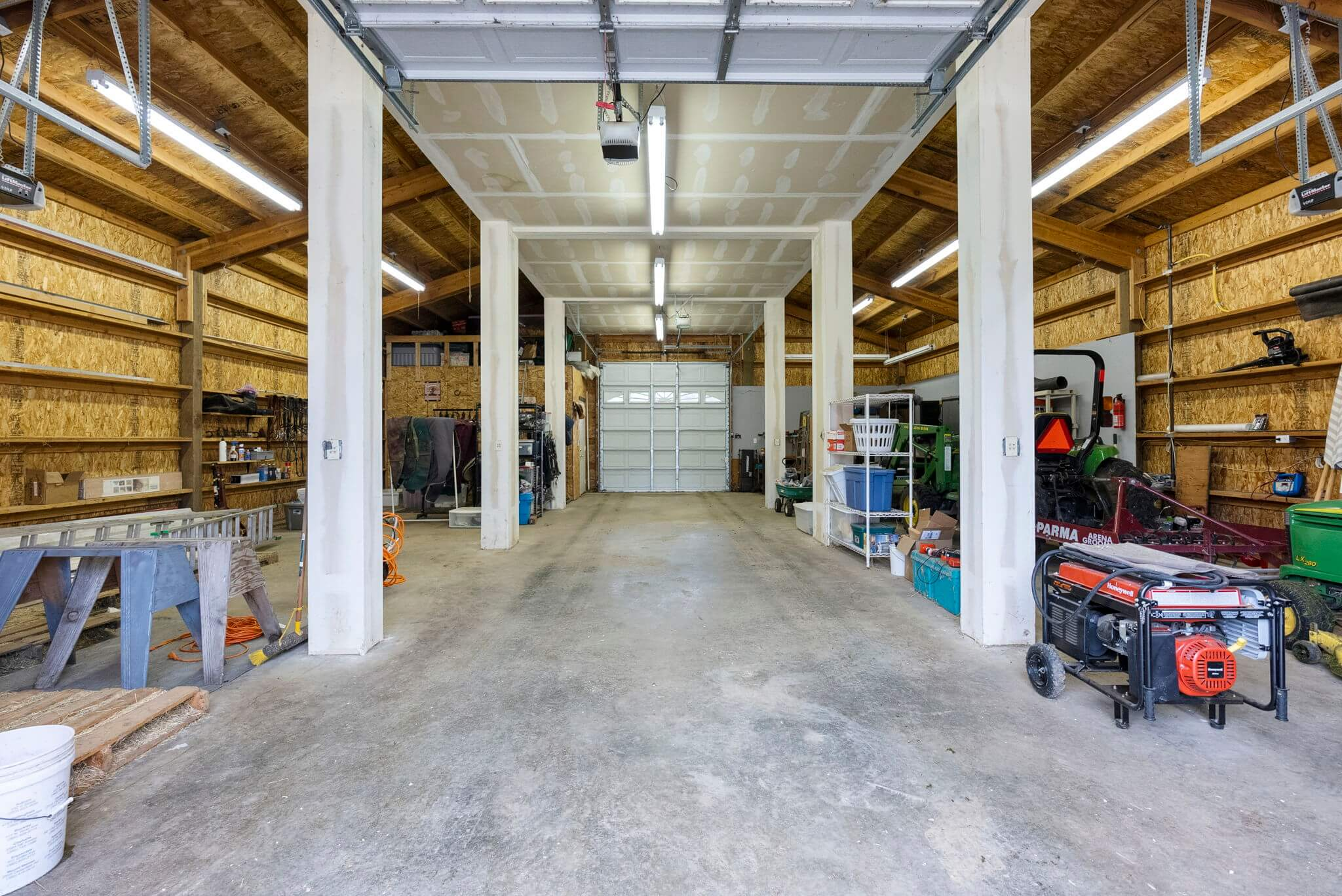 Newer barn with concrete floors is currently used as a shop but could make an excellent show horse barn with the addition of stalls