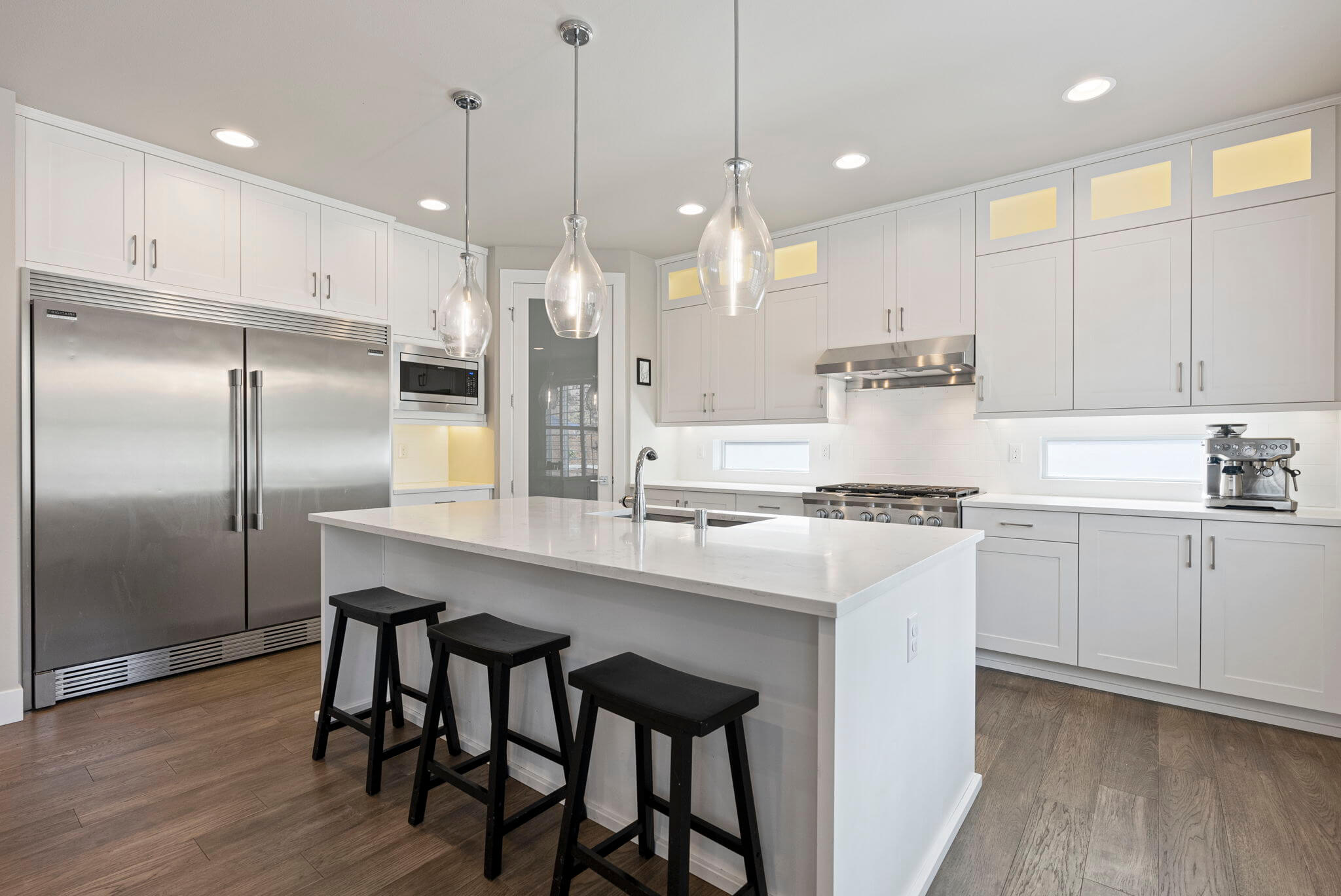 Quartz counters and stainless appliances, including a KitchenAid 6-burner gas range/oven