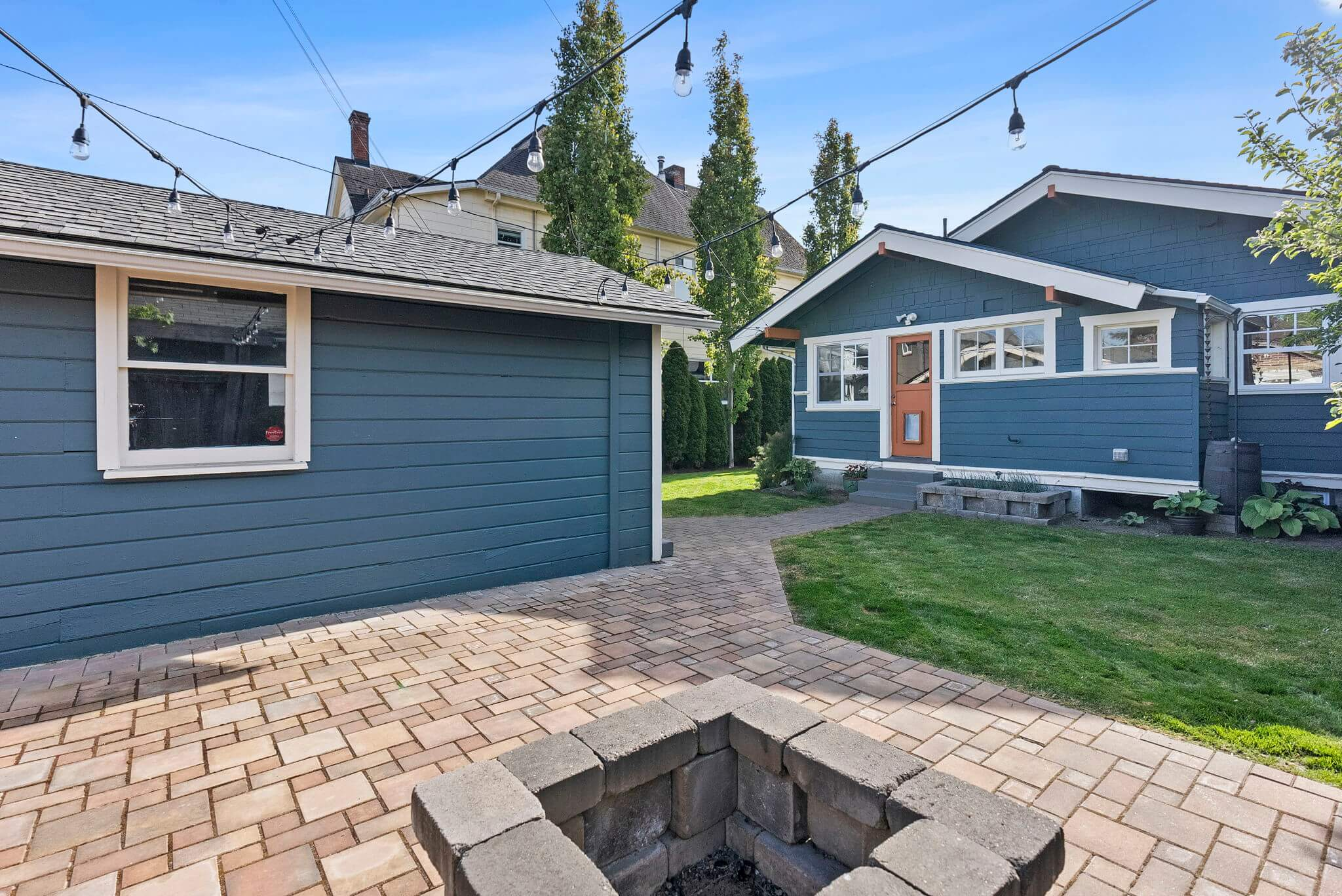 One car garage and paver stone patio with fire pit