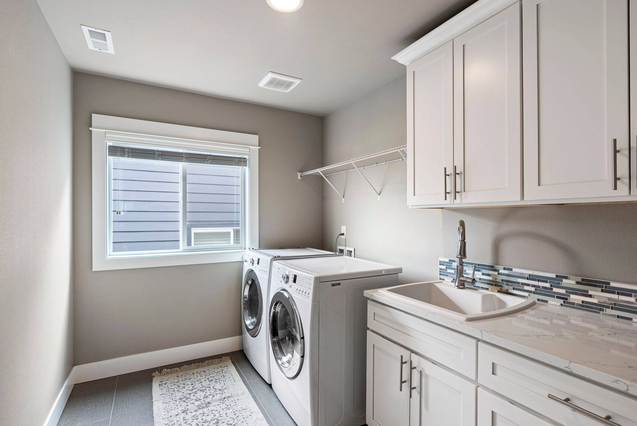 Upstairs laundry room with utility sink and quartz counter