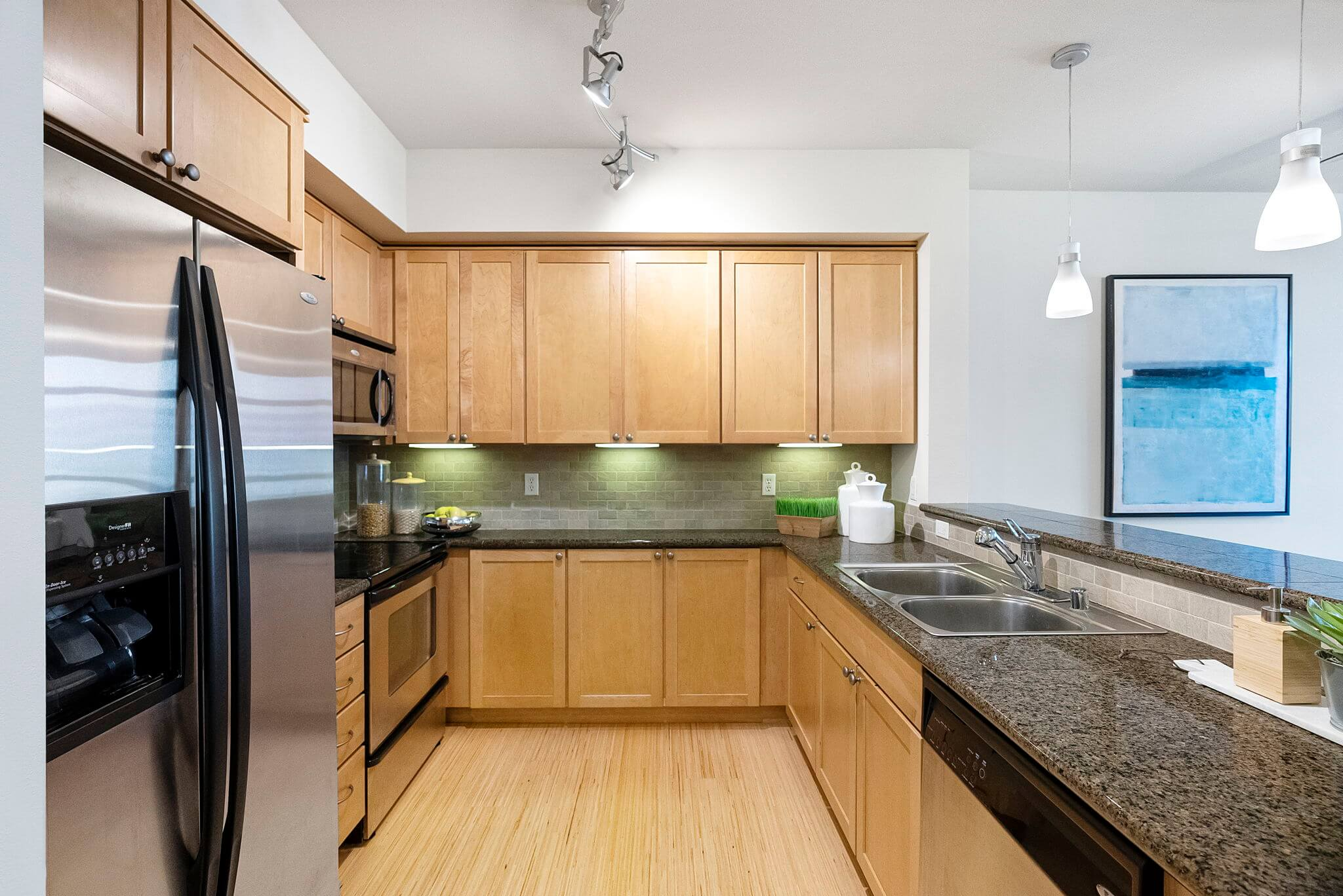 Kitchen features granite counters, stainless appliances, under cabinet lighting and bamboo floors