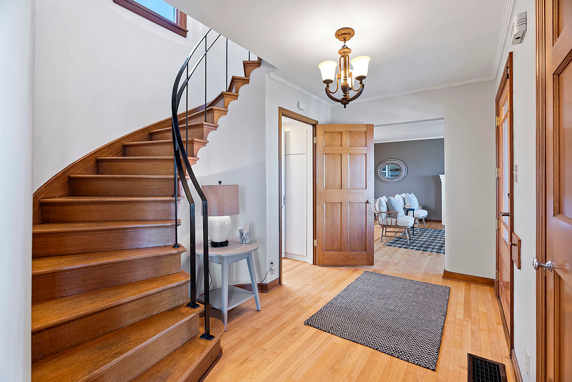 Impressive formal entry with Moderne curved staircase