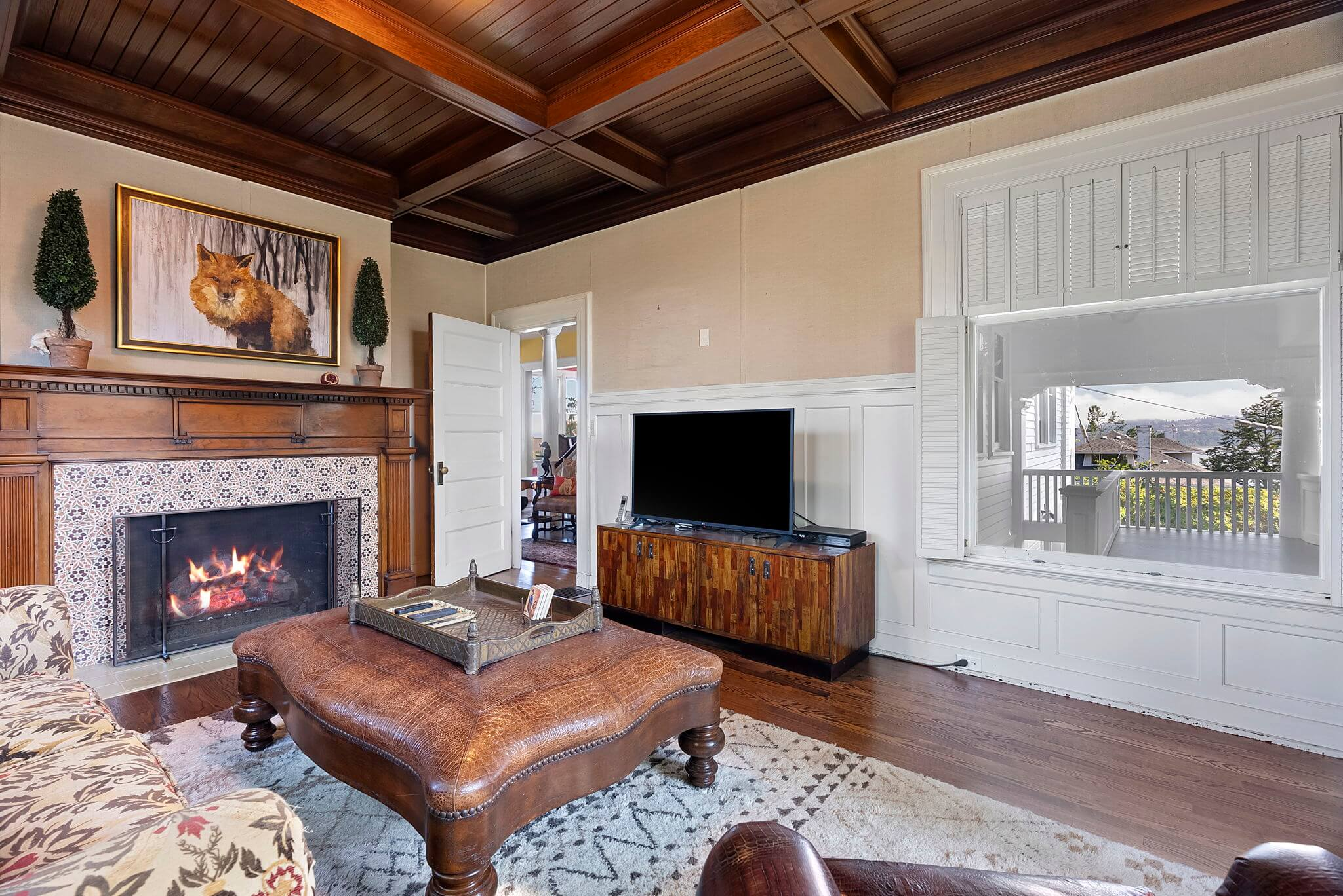 Library features a large fireplace with original mantle and vintage tile surround