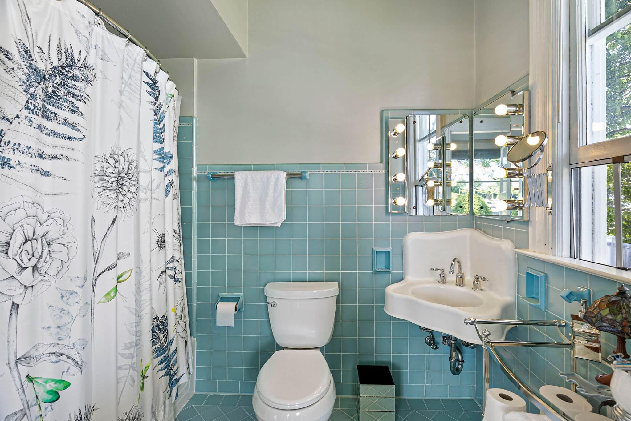 En suite primary bathroom with vintage tile and corner sink