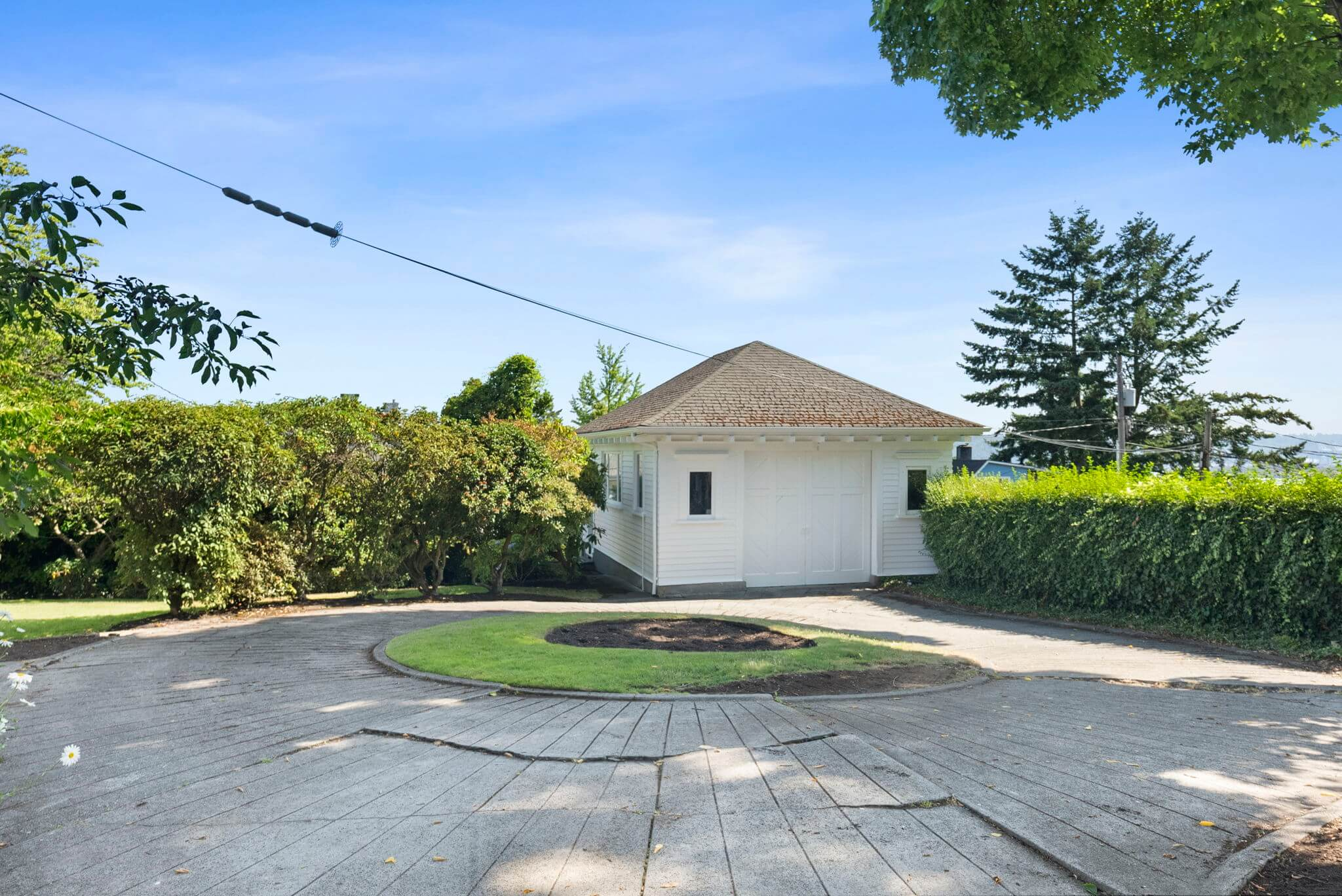Circular driveway beyond the porte-cochere leads to a detached garage