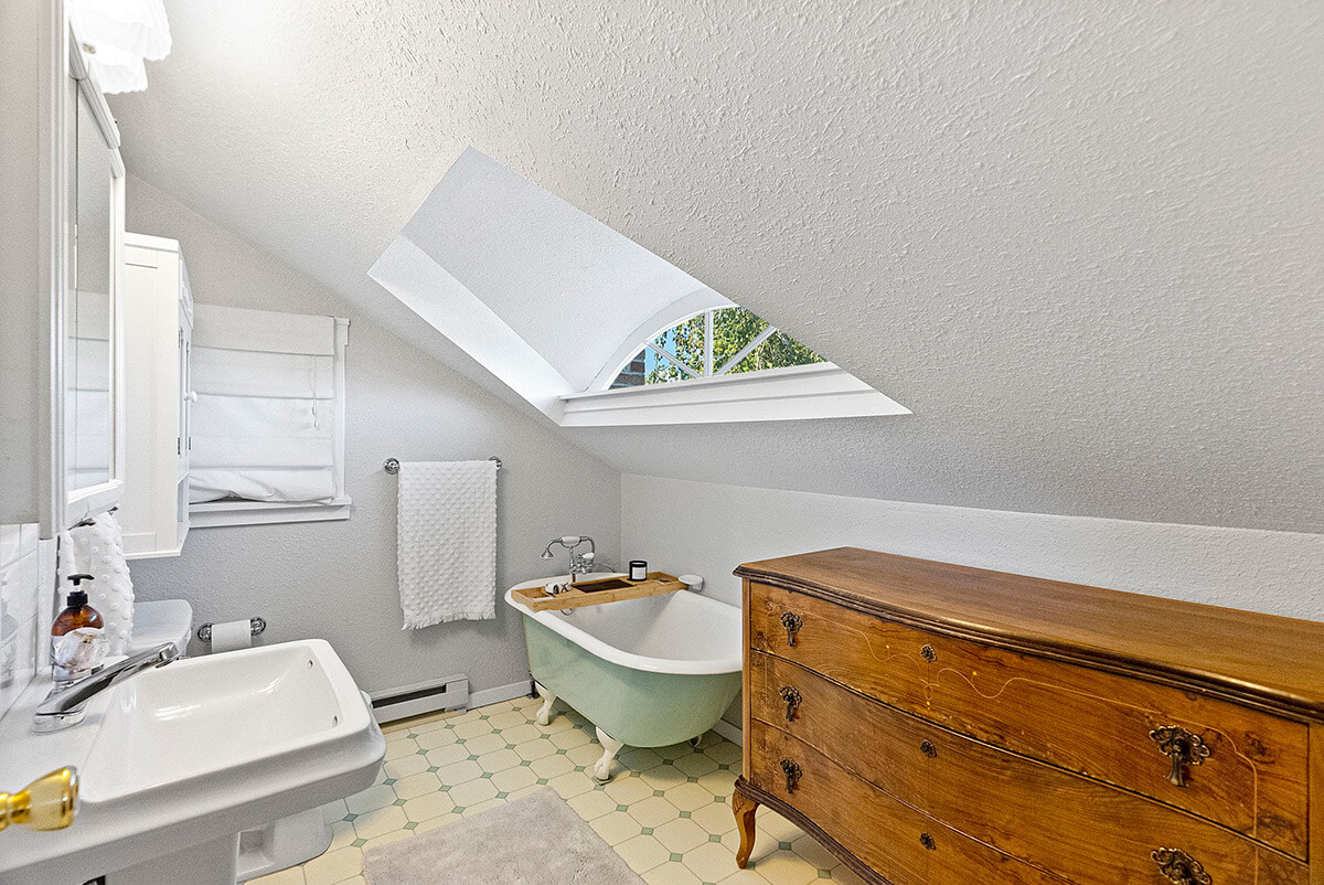 Primary bathroom with claw foot tub and eye brow window